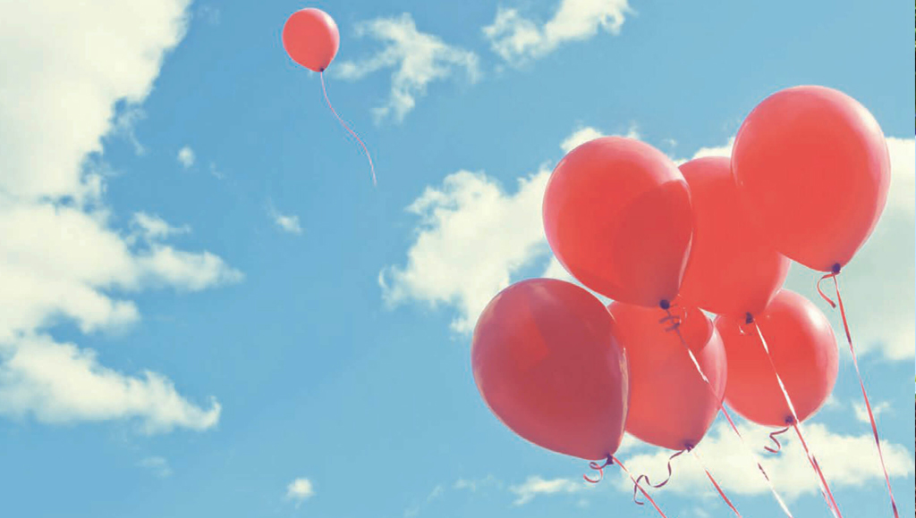 blue sky with red balloons